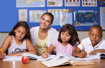 Buy stock photo A young teacher sitting with her three ethnic pupils while they study - portrait