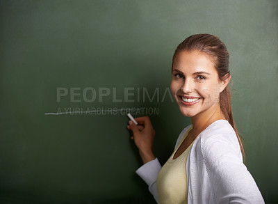 Buy stock photo A beautiful young teacher writing on a blackboard while smiling at the camera - copyspace