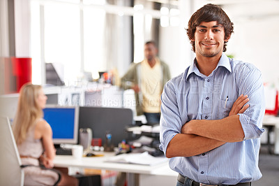 Buy stock photo Shot of a handsome young businessman with his colleagues blurred in the background
