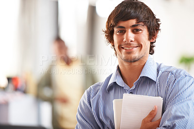 Buy stock photo A handsome young businessman holding his notepad and digital tablet alongside copyspace