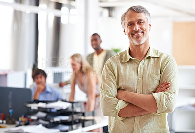 Buy stock photo Shot of a mature businessman with his colleagues blurred in the background