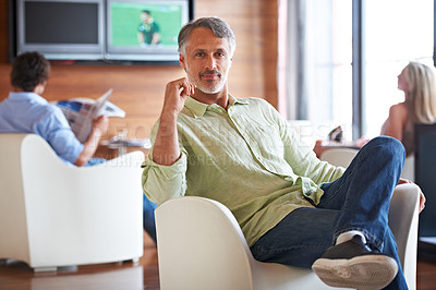 Buy stock photo Shot of a man sitting confidently on a chair indoors