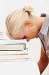 Tensed young female student with head on a stack of books