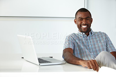 Buy stock photo Handsome young African businessman seated at a desk alongside a laptop