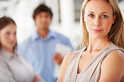 Buy stock photo Shot of a leader smiling at the camera with colleagues blurred in the background