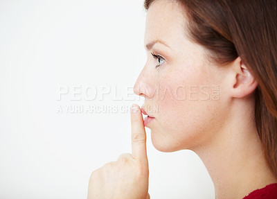 Buy stock photo Profile of a beautiful young woman with her finger on her lips