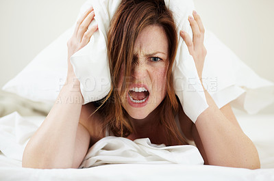 Buy stock photo Portrait of an angry young woman shouting while lying in bed with a pillow over her head