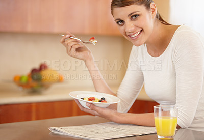Buy stock photo Portrait of an attractive young woman eating her breakfast in the kitchen