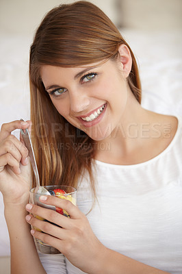 Buy stock photo An attractive young woman eating a fruit salad