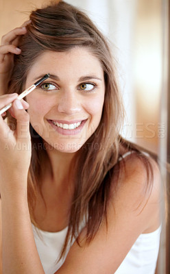 Buy stock photo A beautiful young woman applying eyeliner