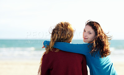 Buy stock photo Rearview portrait of two sisters sitting at the beach