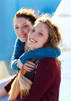 Buy stock photo Portrait of two sister's sitting outside and embracing warmly