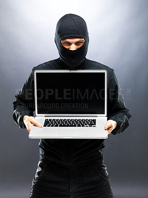 Buy stock photo Portrait of a male robber stealing information from laptop agaisnt grey background