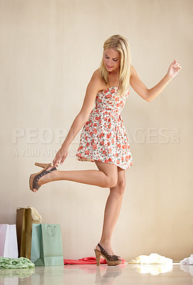 Buy stock photo An attractive young woman putting on her high heels