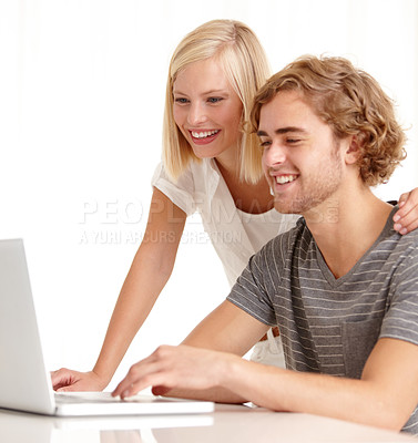 Buy stock photo A young man showing his beautiful girlfriend something on his laptop