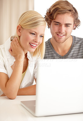Buy stock photo A happy young couple using a laptop to browse the net
