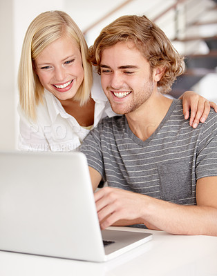 Buy stock photo A young couple using a laptop indoors
