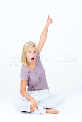 Buy stock photo Astonished young woman pointing upwards