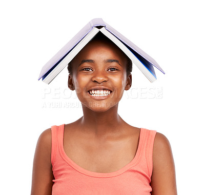 Buy stock photo Studio portrait of a young african girl balancing an open book on her head isolated on white