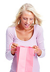 Woman looking into a pink shopping bag over white