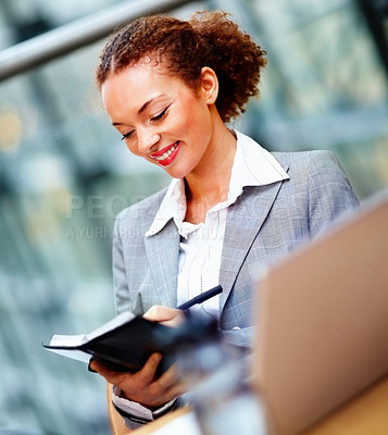 Buy stock photo Happy young business woman writing a note in a small black book