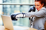 Young business woman in fighting position at work, wearing boxing gloves