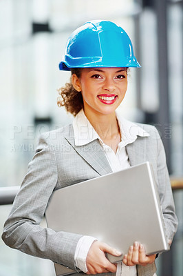 Buy stock photo Portrait of a young business woman with a hardhat holding a laptop