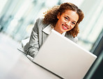 Happy young business woman lying on the floor working on the laptop