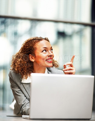 Buy stock photo Young African American business woman using a laptop on the floor, pointing away