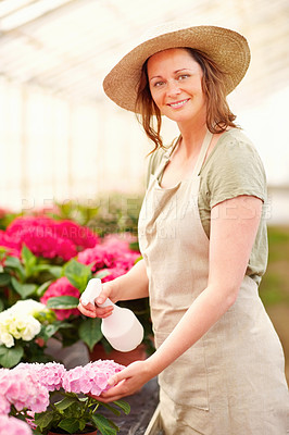 Buy stock photo Happy young woman wearing a hat watering flowers while at a greenhouse