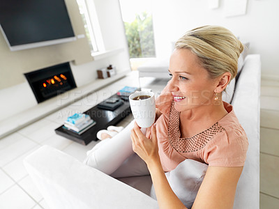Buy stock photo Happy mature woman enjoying a cup of coffee while at her home