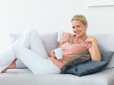 Buy stock photo Happy middle aged woman relaxing on the couch enjoying a cup of coffee