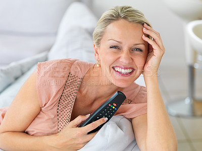Buy stock photo Portrait of a mature woman smiling at home , holding the television remote controller