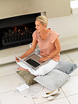 Pretty woman using laptop by a fireplace at home