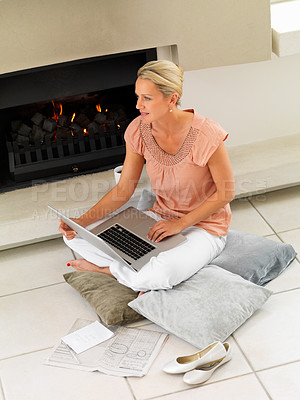 Buy stock photo Mature woman working on laptop by a fireplace , warming herself at home