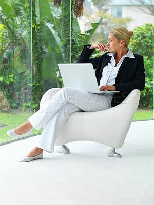 Buy stock photo Mature thoughtful business woman with a laptop in a modern chair, looking outside through glass wall
