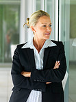 Successful mature business woman standing with hands folded