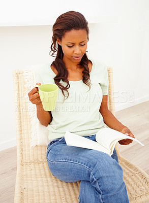 Buy stock photo Casual woman at home reading a book and having coffee
