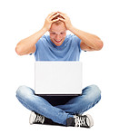 Surprised man sits on the floor with a laptop, isolated on white