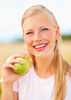 Buy stock photo Portrait of a happy young female eating a green apple outside