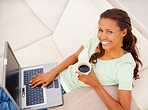 A happy woman using laptop at home