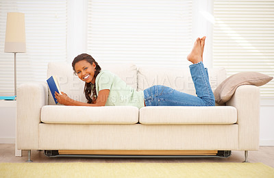 Buy stock photo Portrait of a happy young female relaxing on the couch, reading a novel