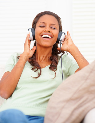 Buy stock photo Young African American woman listening to music on the headphones