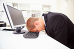 A tired businessman with his forehead resting on the keyboard