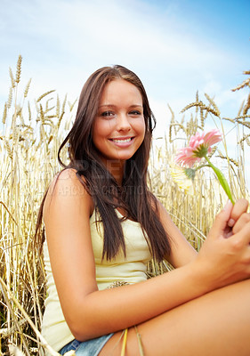 Buy stock photo Portrait of a lovely young woman sitting in a wheat field holding a summer flower - copyspace