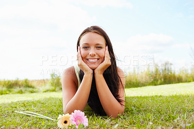 Buy stock photo Portrait of a happy young female lying at the park on a pleasant day