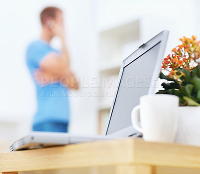 Buy stock photo Man speaking on the mobile, focus on laptop on the table