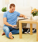 Relaxed young guy browsing the internet using a laptop at home
