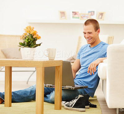 Buy stock photo Healthy lifestyle - Young guy relaxed at home browsing the net on a laptop