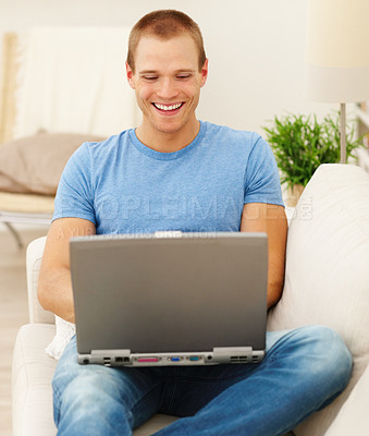 Buy stock photo Portrait of a happy young man using a laptop at home